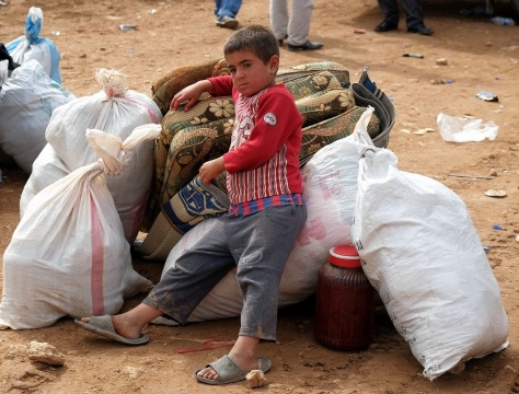 A young boy sits at the Turkish border crossing after fleeing fighting in Syria