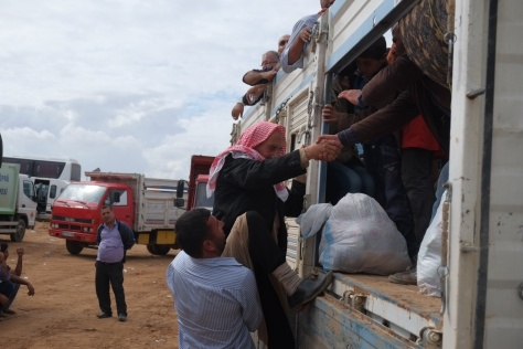 an old man is helped into a truck at the Turkish border which will then drive refugees to camps set up by the government